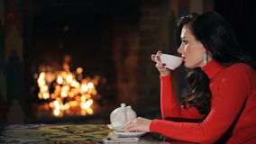 Profile of brunette in red sweater, drinking tea indoor. stock footage
