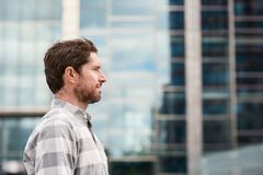 Profile of a young man standing alone in the city. Profile of a casually dressed young man standing alone in front of buildings on a street in the city stock images