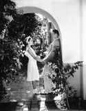 Profile of a couple romancing in an archway Stock Images