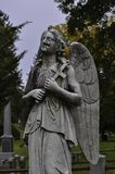 Profile of a Damaged Angel Statue in a Cemetery. Profile of a damaged angel statue holding a cross, with closed eyes, in a cemetery royalty free stock images