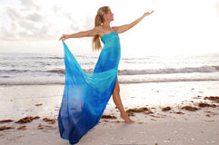 Profile of dancer. A female dancer is posing in profile with arms raised and looking at her open hand at the beach with waves crashing in the background Royalty Free Stock Photos