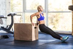 Profile side. Woman doing push up on cross fit coub. stock photos