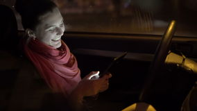 Profile of emotional girl sitting in the car and using tablet. 4K stock video