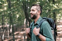 Cheerful male tourist hiking in the woods. Profile of excited young man admiring the nature in the forest. He is standing with backpack and smiling. Copy space Royalty Free Stock Photos