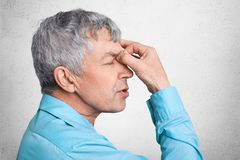 Profile of exhausted grey haired male in formal shirt, keepd hands on nose, poses against white concrete background, tries to conc. Entrate and find solution in Stock Photography