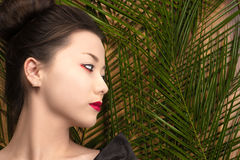 Profile face attractive young Korean girl with tropical bushes Stock Image