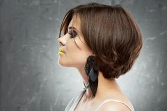 Profile face portrait of woman with medium length hair . b. Ob haircut. big black earring royalty free stock image