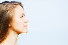Profile of the face of the young woman. The young girl looks afar against the sky Stock Photography