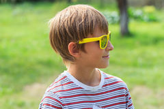 Profile of fair-haired teenage boy wearing yellow mirror sunglasses Stock Photography