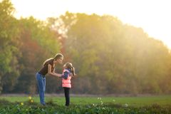 Profile full-length portrait of young slim attractive mother talking to child girl standing in green meadow holding hands outdoors. On forest trees blurred royalty free stock photos