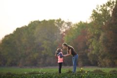 Profile full-length portrait of young slim attractive mother talking to child girl standing in green meadow holding hands outdoors royalty free stock photography