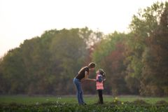 Profile full-length portrait of young slim attractive mother talking to child girl standing in green meadow holding hands outdoors royalty free stock image