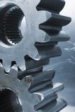 Profile of gears against aluminum. Two gear-wheels in blue against bluish aluminum Stock Image