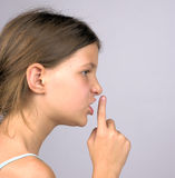 Profile of girl with finger on lips. Portrait (profile) of a shushing young girl with the gesture of one finger on the lips, against a blue background stock photography