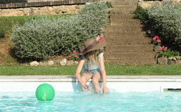 Profile of a girl with hat playing at pool's edge. Profile of a girl wearing a brown hat and playing in the swimming pool, hands and feet in the water Stock Image