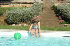 Profile of a girl with hat playing at pool's edge Stock Image