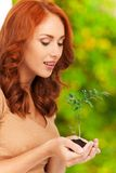 Profile of girl holding little plant in her hands. Royalty Free Stock Images