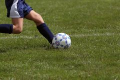 Profile of girl kicking soccer ball stock images