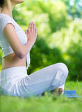 Profile of girl in lotus position prayer gesturing Stock Photos