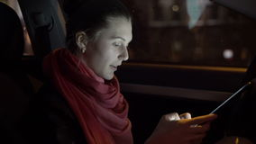 Profile of girl sitting in the car and using a tablet, 4K stock footage