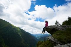 Profile girl sitting on rock, dangling her legs in abyss stock photo