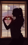 A profile of girl which is standing by window and making heart with her hands. Romantic mood. Sunset. Silhouette. Royalty Free Stock Photo