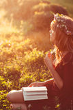 Profile of girl in wreath with book, sun flare Stock Photos