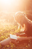 Profile of girl in wreath reading book, sun flare Stock Photos