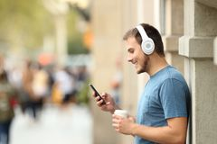 Profile of a guy listening music on line on the street. Profile of a happy guy listening music on line with headphones and a smart phone leaning on a wall on the Stock Image