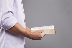 Profile of Hands holding Bible. A man stands indoors holding a bible out in front of him with both hands Royalty Free Stock Photos