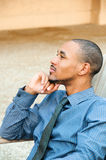 Profile Handsome Black American Man. Profile of a young, well dressed, handsome African American male sitting in a chair pensively looking out in the distance Royalty Free Stock Photos
