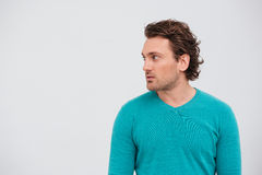 Profile of handsome curly young man standing and looking away Royalty Free Stock Images
