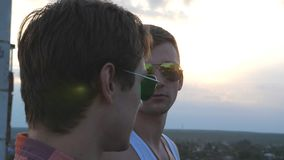 Profile of handsome gay boys in sunglasses standing on the edge of rooftop and talking. Young male couple relaxing on. Roof of high-rise building and enjoying stock footage