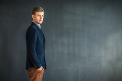 Profile of handsome man standing against grey wall background Stock Photography