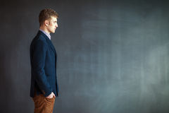 Profile of handsome man standing against grey wall background Stock Image
