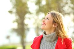 Profile of a woman looking above in winter. Profile of a happy fashion woman wearing a red jacket looking above in winter Stock Photography