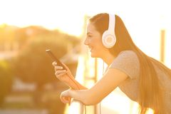 Profile of a happy girl listening music in a balcony. Side view portrait of a happy girl listening music with headphones and smart phone in a house balcony at Royalty Free Stock Photo