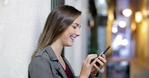 Profile of a girl using a phone in the night. Profile of a happy girl using a smart phone in the night in the street of an old town
