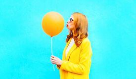 Profile happy woman kisses an air balloon in yellow coat on blue Stock Image