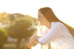 Profile of a happy woman looking away in a balcony. Side view portrait of a happy brunette woman looking away in a balcony at sunset stock images