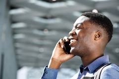 Profile of happy young african american man talking on cellphone. Profile portrait of happy young african american man talking on cellphone royalty free stock image