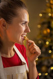 Profile happy young housewife eating walnuts Stock Image