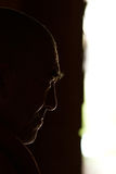 Profile head of a monk in backlit conditions Royalty Free Stock Images