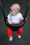 Profile of a little baby boy with pacifier in her mouth in the swing Stock Photo
