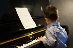 Profile of a little boy learning piano Royalty Free Stock Photography