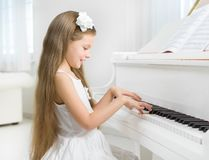 Profile of little girl in white dress playing piano Royalty Free Stock Photography