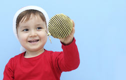Profile of a little  kid dressed as santa claus with a golden bauble in his hand Stock Photo