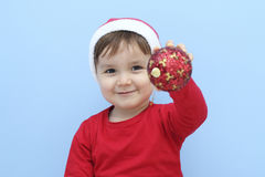Profile of a little  kid dressed as santa claus with a red bauble in his hand Royalty Free Stock Photography