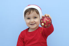 Profile of a little  kid dressed as santa claus with a red bauble in his hand Stock Photography