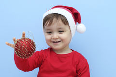 Profile of a little  kid dressed as santa claus with a red bauble in his hand Royalty Free Stock Photos